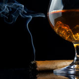 Snifter glass of cognac and cigar. On black Royalty Free Stock Photo