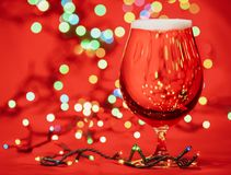 Glass of pale lager beer or ale with christmas lights on red background stock photo