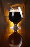 Snifter of stout. Snifter glass with black stout beer on a wooden table with a warm colored drapery in the background Royalty Free Stock Images