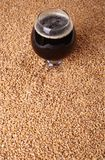 Snifter with stout over malt Royalty Free Stock Photos