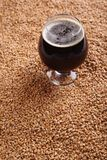Snifter with stout over malt Stock Photos
