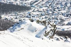 Snöig vaggar, vinterlandskapet och byn i dalen Royaltyfri Foto