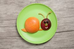 Snigel som göras med frukter på plattan och tabellen Royaltyfri Fotografi