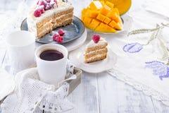 Snijd de cake met witte room, voor het fruit van de ontbijta mango Witte achtergrond, tafelkleed met kant, een kop van koffie en  stock foto