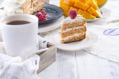 Snijd de cake met witte room, voor het fruit van de ontbijta mango Witte achtergrond, tafelkleed met kant, een kop van koffie en  stock afbeeldingen