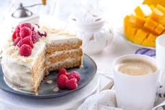 Snijd de cake met witte room, voor het fruit van de ontbijta mango Witte achtergrond, tafelkleed met kant, een kop van koffie en  royalty-vrije stock afbeeldingen