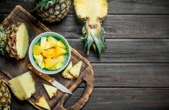 Snijd een ananas in een kom en op een scherpe Raad met een mes stock foto's