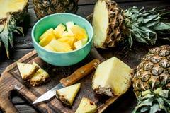 Snijd een ananas in een kom en op een scherpe Raad met een mes stock fotografie