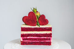 Snijd een kleine rood-en-witte die cake, met rozen en harten wordt verfraaid Royalty-vrije Stock Afbeelding