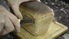 Snijd een stuk van zwart brood stock video