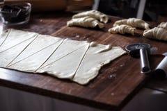 Snijd het deeg in driehoeken voor croissants met chocolade royalty-vrije stock afbeeldingen