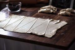 Snijd het deeg in driehoeken voor croissants met chocolade royalty-vrije stock foto's