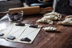 Snijd het deeg in driehoeken voor croissants met chocolade stock foto