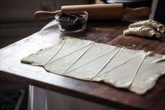 Snijd het deeg in driehoeken voor croissants met chocolade royalty-vrije stock foto