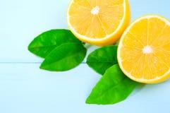 Snijd vers halve citroenen met bladeren op blauwe houten oppervlakte stock afbeeldingen