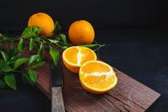 Snijd vers oranje fruit op een houten scherpe raad zwarte backgr stock foto