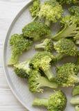 Snijd vers ruwe broccoli op grijze plaat over witte houten oppervlakte, hoogste mening Vlak leg hierboven, van, overheadkosten stock fotografie