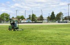 Snijdend het gras van het spelen van gebied Stock Foto
