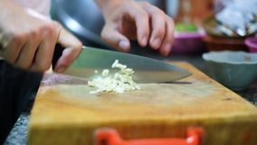 Snijdend knoflook op scherpe raad om ingrediënt voor te bereiden stock videobeelden