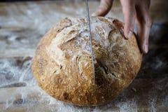 Snijdend vers eigengemaakt die brood van zuurdesem wordt gemaakt Artisanaal brood met gouden knapperige korst stock afbeelding