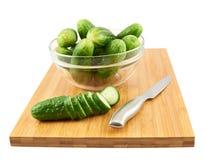 Snijdende komkommer over een scherpe raad Stock Fotografie