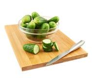 Snijdende komkommer over een scherpe raad Royalty-vrije Stock Afbeeldingen