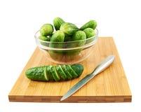 Snijdende komkommer over een scherpe raad Stock Afbeeldingen