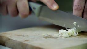 Snijdende prei op houten bureau stock video