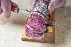 Snijdende salami Stock Foto