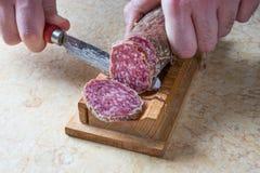 Snijdende salami Stock Fotografie