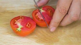 Snijdende tomaat op scherpe raad stock footage