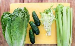 Snijslasalade, komkommer, fries, selderie op een raad op een houten achtergrond Stock Foto