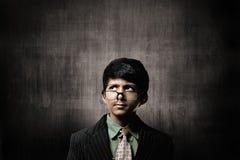 SnilleLittle Boy bärande exponeringsglas som tänker nära den svart tavlan Royaltyfri Foto