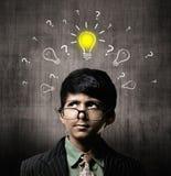 SnilleLittle Boy bärande exponeringsglas, tänkande idé nära den svart tavlan royaltyfria foton