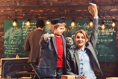Snillepojken undervisar kvinnan och mannen på den svart tavlan Snillesonen med modern och fadern har kurs i klassrumet som lär oc fotografering för bildbyråer