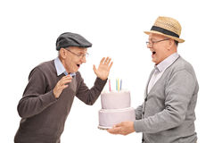 Sênior alegre que traz o bolo a seu amigo Imagem de Stock Royalty Free