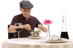 Sênior em uma tabela do restaurante que come uma salada Foto de Stock Royalty Free