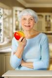 Sênior idoso da mulher com a maçã vermelha em sua mão na cozinha Fotografia de Stock Royalty Free