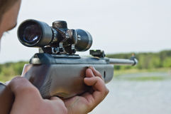 Sniper. The young man with a sniper rifle aims against a decline Royalty Free Stock Image