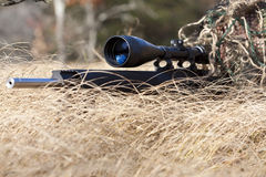 Sniper. Laying on the ground covered in a ghille suite tall grass and trees in the background Royalty Free Stock Images