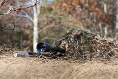 Sniper. Laying on the ground covered in a ghille suite tall grass and trees in the background Stock Images