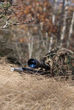 Sniper. Laying on the ground covered in a ghille suite tall grass and trees in the background Stock Photo