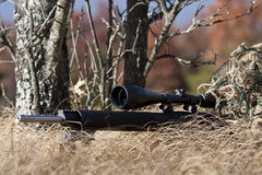 Sniper. Laying on the ground covered in a ghille suite tall grass and trees in the background Stock Photos