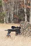 Sniper. Laying on the ground covered in a ghille suite tall grass and trees in the background Royalty Free Stock Image