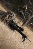 Sniper. Laying on the ground covered in a ghille suite tall grass and trees in the background Royalty Free Stock Photography