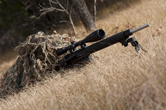 Sniper. Laying on the ground covered in a ghille suite tall grass and trees in the background Stock Photography