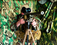 Sniper. Man as a sniper or precision shooter outfitted in camouflage with bolt action rifle in an indoor hide setting Royalty Free Stock Images