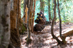 Sniper Aiming Gun. Paintball sport player in protective uniform and mask aiming gun before shooting royalty free stock image