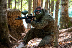 Sniper Aiming Gun. Paintball sport player in protective uniform and mask aiming and shooting with gun outdoors royalty free stock photos