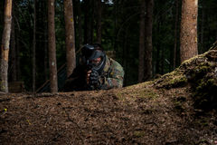Sniper Aiming Gun. Paintball sport player in protective uniform and mask aiming and shooting with gun outdoors stock image